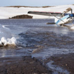 Bill Martin, owner of Cold Bay Lodge, plane frozen in the ice in Cold Bay